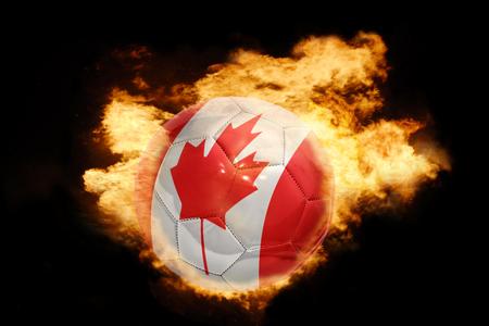 banderas america: pelota de fútbol con la bandera nacional de canadá en el fuego sobre un fondo negro