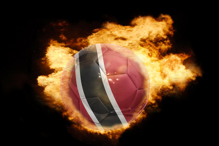 national flag trinidad and tobago: football ball with the national flag of trinidad and tobago on fire on a black background