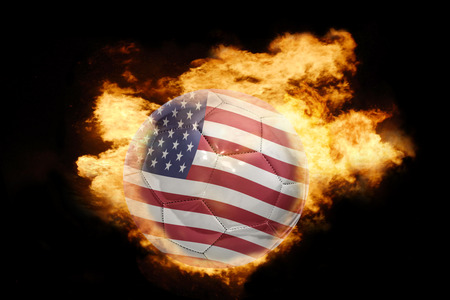 central america: football ball with the national flag of united states of america on fire on a black background
