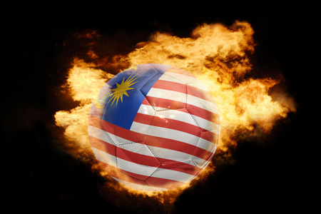 goal flag: football ball with the national flag of malaysia on fire on a black background Stock Photo