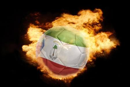 equatorial guinea: football ball with the national flag of equatorial guinea on fire on a black background Stock Photo