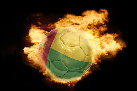 guinea bissau: football ball with the national flag of guinea bissau on fire on a black background