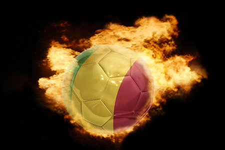 bamako: football ball with the national flag of mali on fire on a black background