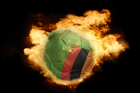 zambian: football ball with the national flag of zambia on fire on a black background