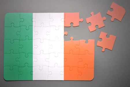 separatism: broken puzzle with the national flag of ireland on a gray background