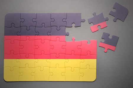 separatism: broken puzzle with the national flag of germany on a gray background
