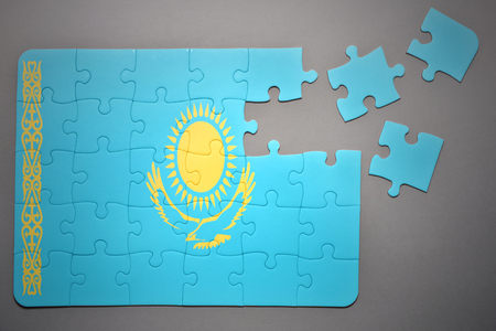 separatism: broken puzzle with the national flag of kazakhstan on a gray background Stock Photo
