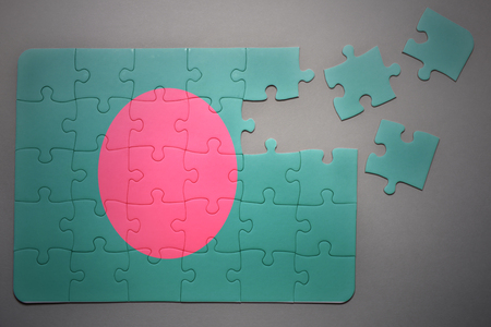 separatism: broken puzzle with the national flag of bangladesh on a gray background Stock Photo