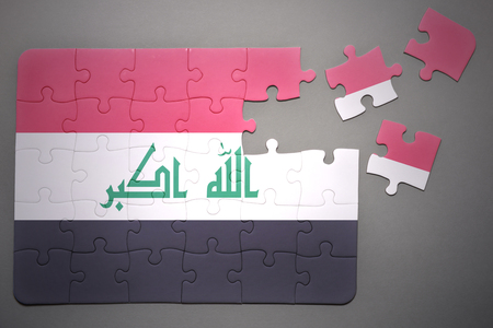 separatism: broken puzzle with the national flag of iraq on a gray background Stock Photo