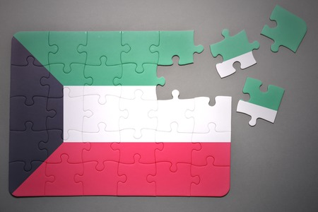 separatism: broken puzzle with the national flag of kuwait on a gray background