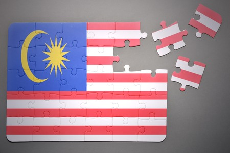 malaysia: broken puzzle with the national flag of malaysia on a gray background