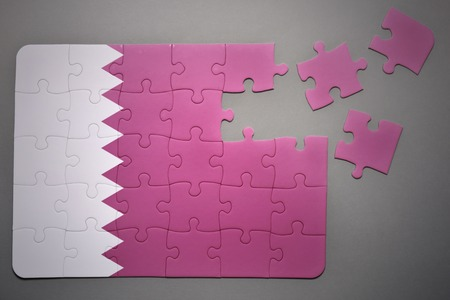 separatism: broken puzzle with the national flag of qatar on a gray background Stock Photo