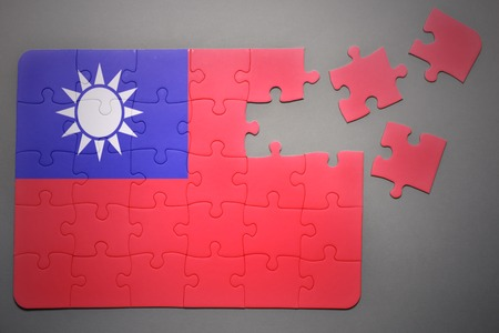 separatism: broken puzzle with the national flag of taiwan on a gray background