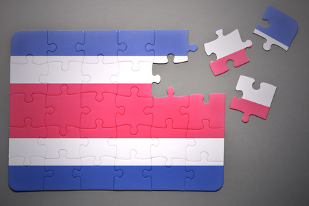 costa rican flag: broken puzzle with the national flag of costa rica on a gray background Stock Photo