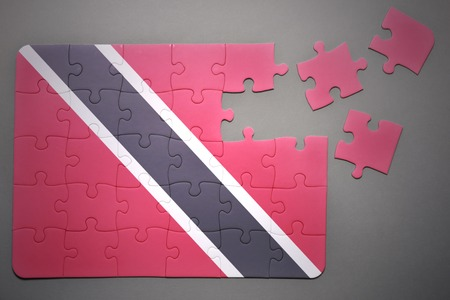 national flag trinidad and tobago: broken puzzle with the national flag of trinidad and tobago on a gray background