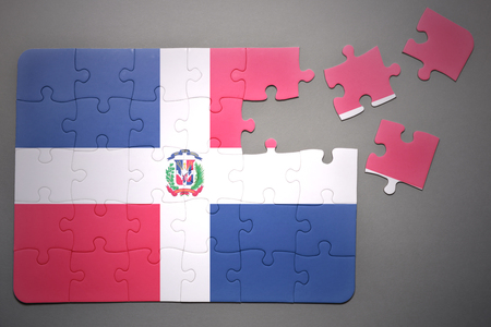 separatism: broken puzzle with the national flag of dominican republic on a gray background