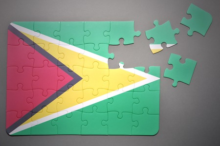 separatism: broken puzzle with the national flag of guyana on a gray background