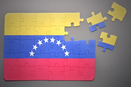 separatism: broken puzzle with the national flag of venezuela on a gray background Stock Photo