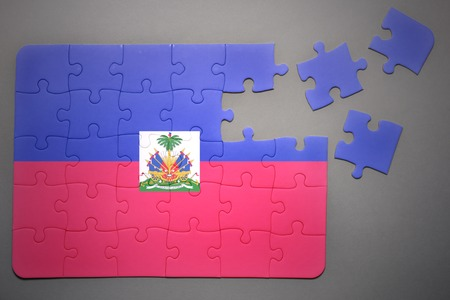 port au prince: broken puzzle with the national flag of haiti on a gray background