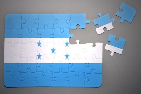 separatism: broken puzzle with the national flag of honduras on a gray background