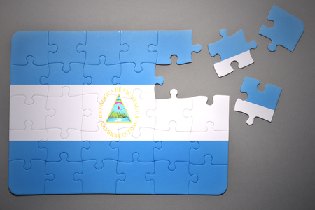 separatism: broken puzzle with the national flag of nicaragua on a gray background