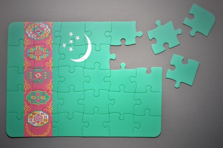 separatism: broken puzzle with the national flag of turkmenistan on a gray background