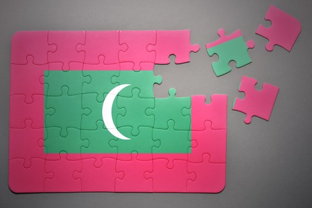 separatism: broken puzzle with the national flag of maldives on a gray background