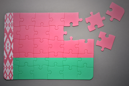 separatism: broken puzzle with the national flag of belarus on a gray background
