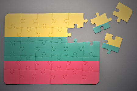 separatism: broken puzzle with the national flag of lithuania on a gray background Stock Photo