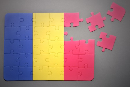 separatism: broken puzzle with the national flag of romania on a gray background