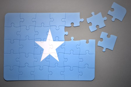 separatism: broken puzzle with the national flag of somalia on a gray background Stock Photo