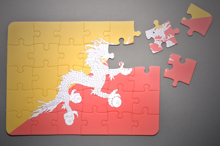 separatism: broken puzzle with the national flag of bhutan on a gray background