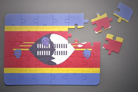 separatism: broken puzzle with the national flag of swaziland on a gray background
