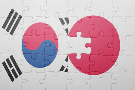 south korea flag: puzzle with the national flag of japan and south korea . concept