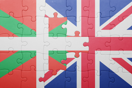 the basque country: puzzle with the national flag of great britain and Basque Country . concept
