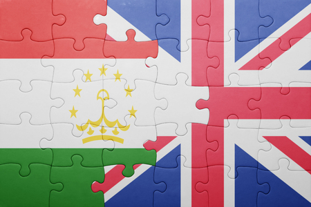 economy of tajikistan: puzzle with the national flag of great britain and tajikistan . concept