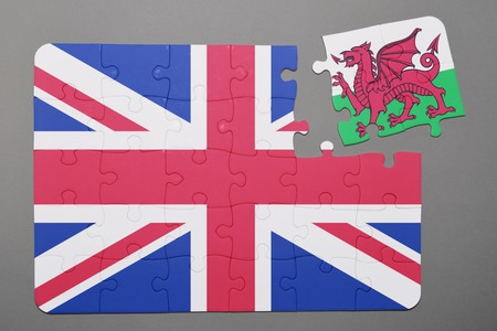 separatism: Puzzle with national flag of great britain and wales piece detached. Concept