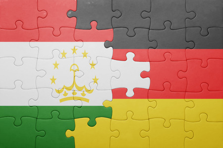 economy of tajikistan: puzzle with the national flag of germany and tajikistan. concept