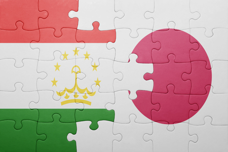 economy of tajikistan: puzzle with the national flag of tajikistan and japan. concept