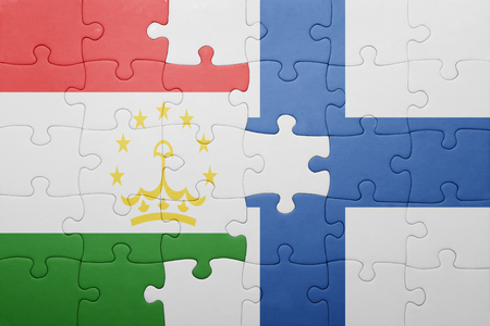 economy of tajikistan: puzzle with the national flag of tajikistan and finland . concept