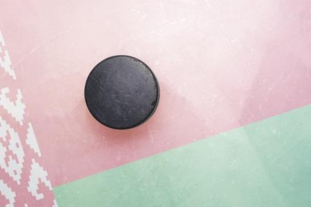 hockey hielo: vendimia viejo disco de hockey está en el hielo con la bandera de bielorrusia