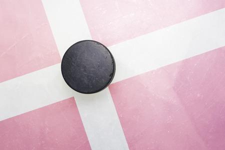hockey hielo: vendimia viejo disco de hockey está en el hielo con el indicador de Dinamarca Foto de archivo