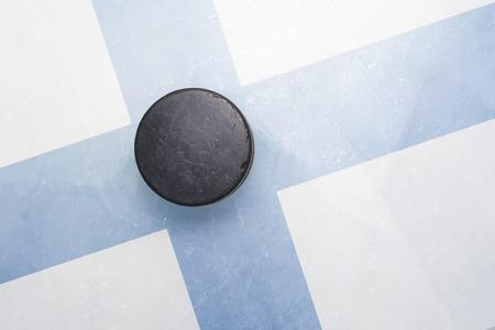hockey hielo: vendimia viejo disco de hockey está en el hielo de la bandera de Finlandia Foto de archivo