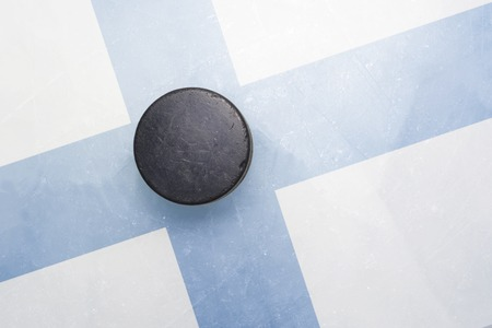 vintage old hockey puck is on the ice with finland flag Stock Photo