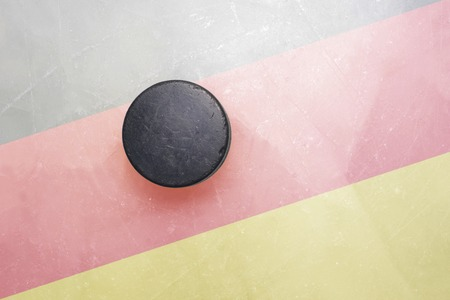 hockey hielo: vendimia viejo disco de hockey está en el hielo con el indicador de Alemania Foto de archivo