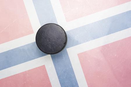 hockey hielo: vendimia viejo disco de hockey está en el hielo con la bandera noruega