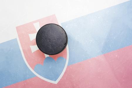 hockey hielo: vendimia viejo disco de hockey está en el hielo con la bandera de Eslovaquia
