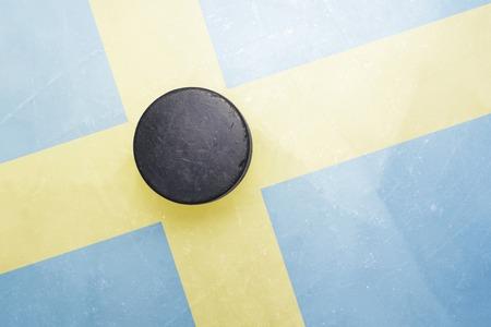 hockey hielo: vendimia viejo disco de hockey está en el hielo con el indicador de Suecia