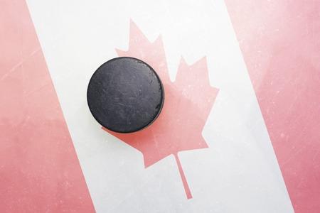 hockey sobre hielo: vendimia viejo disco de hockey está en el hielo con el indicador de Canadá Foto de archivo