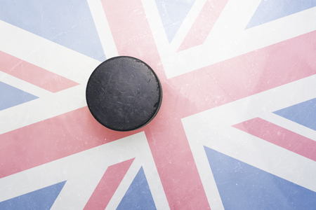 gb: vintage old hockey puck is on the ice with great britain flag Stock Photo